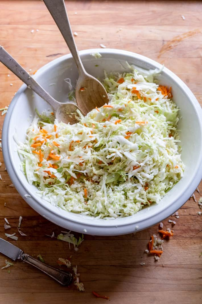 Freshly shredded cabbage and carrots added to large bowl of slaw dressing.