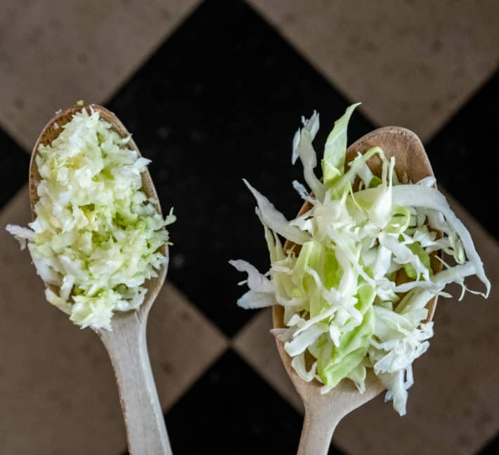 Side by side wooden spoons showcasing food processed shredded cabbage compared to hand shredded.