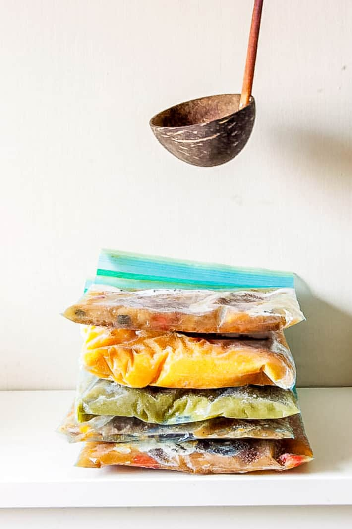 Colourful bags of soup stacked on top of each other straight out of the freezer.