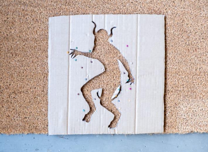 Cardboard DIY doormat stencil pinned to coir mat.