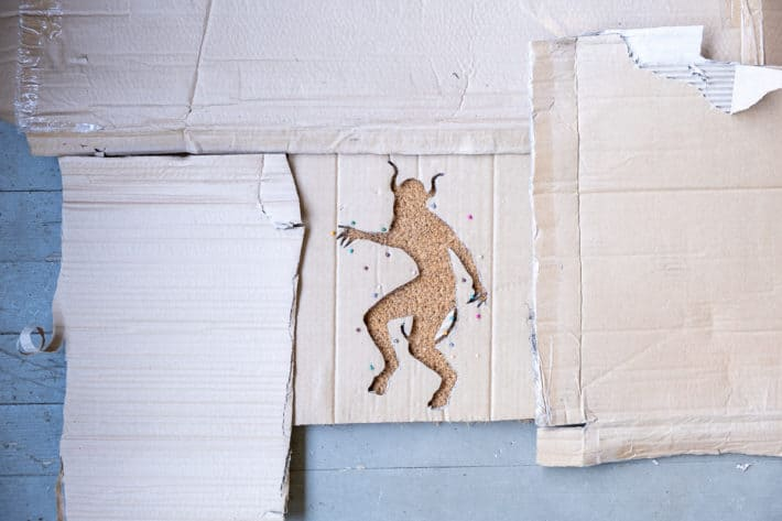 Cardboard covering a coir doormat before spraying with paint.