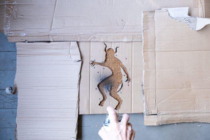 Spraying coir mat with a cardboard stencil on it.
