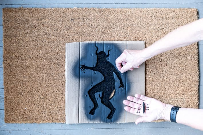 Removing pins that were holding stencil on doormat.