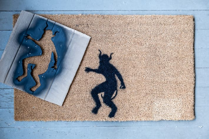Stencil sits beside finished product on black painted diy halloween doormat.
