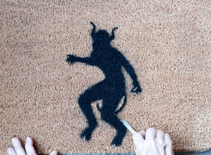 Cleaning up a stencilled doormat with scissors.