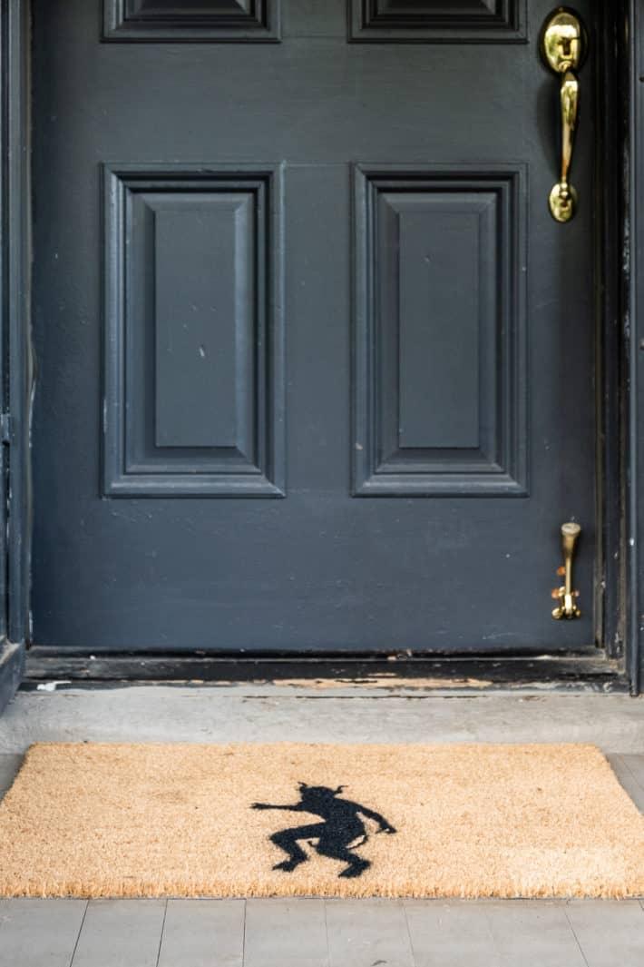 DIY demon Halloween doormat sits outside black painted front door.