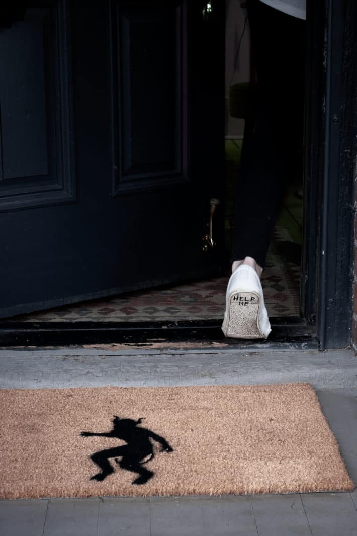 "Coir doormat with demon printed on it, sole of running shoe with ""help me"" written on it seen walking through a door above."