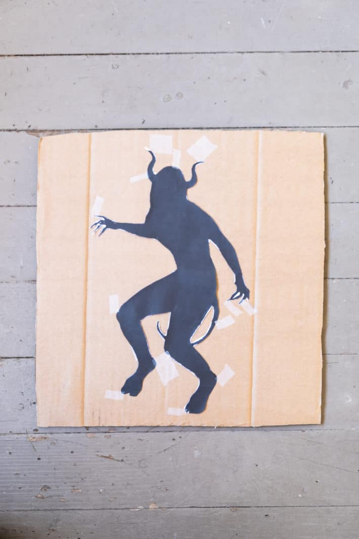 Demon silhouette cutout taped to cardboard.