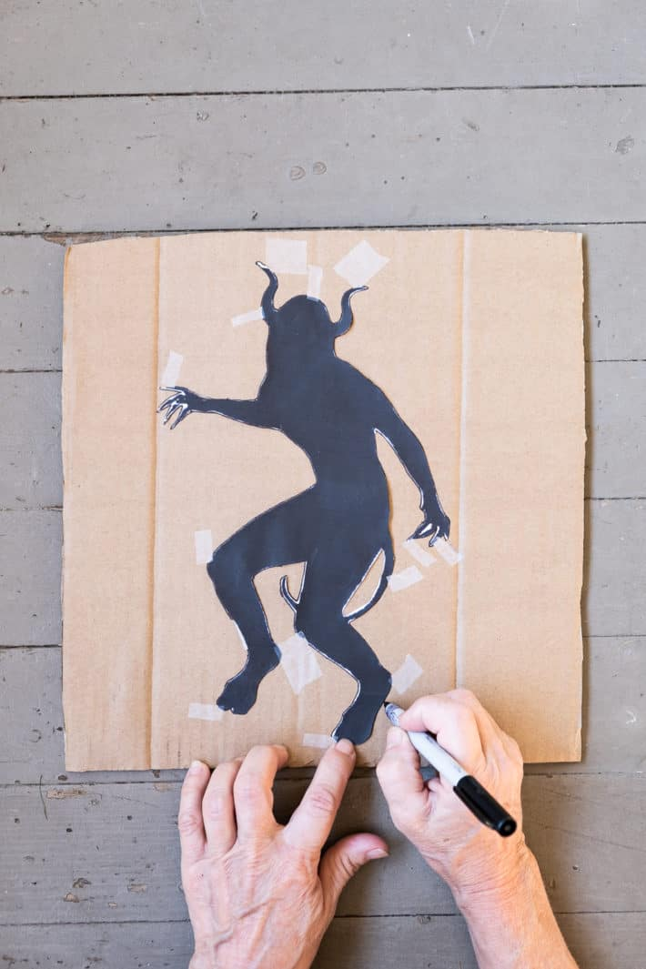 Tracing outline of demon on cardboard with Sharpie.