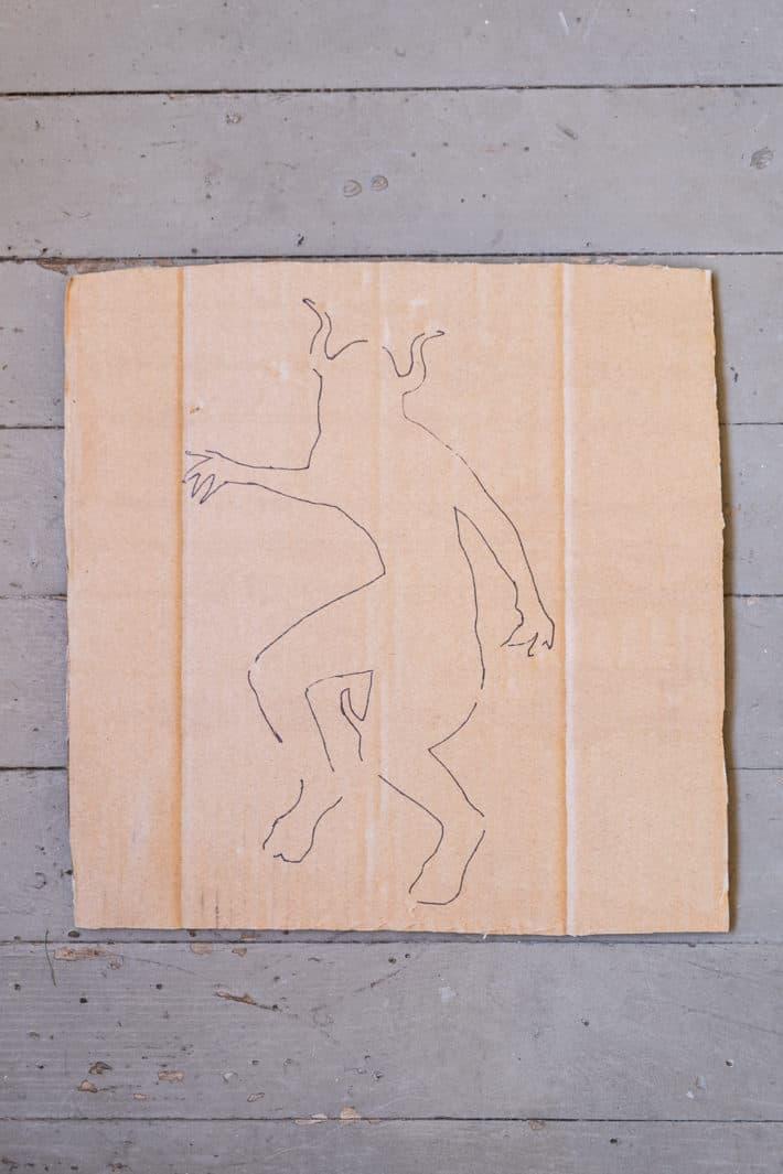 Outline for DIY doormat on cardboard.