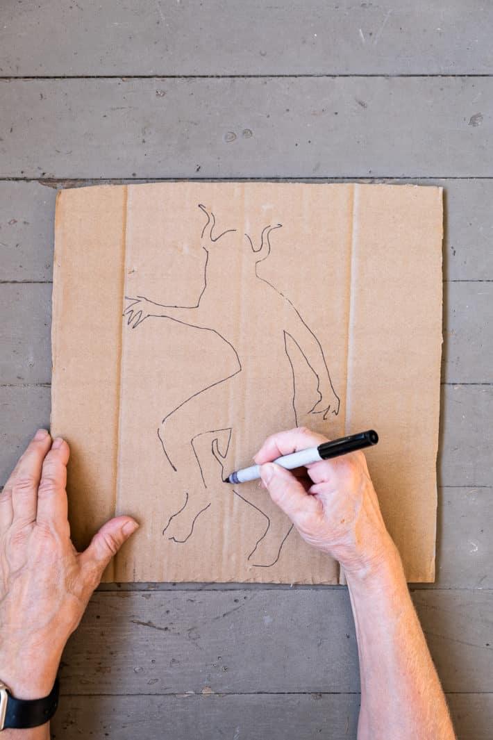 Drawing demon outline for DIY halloween doormat.