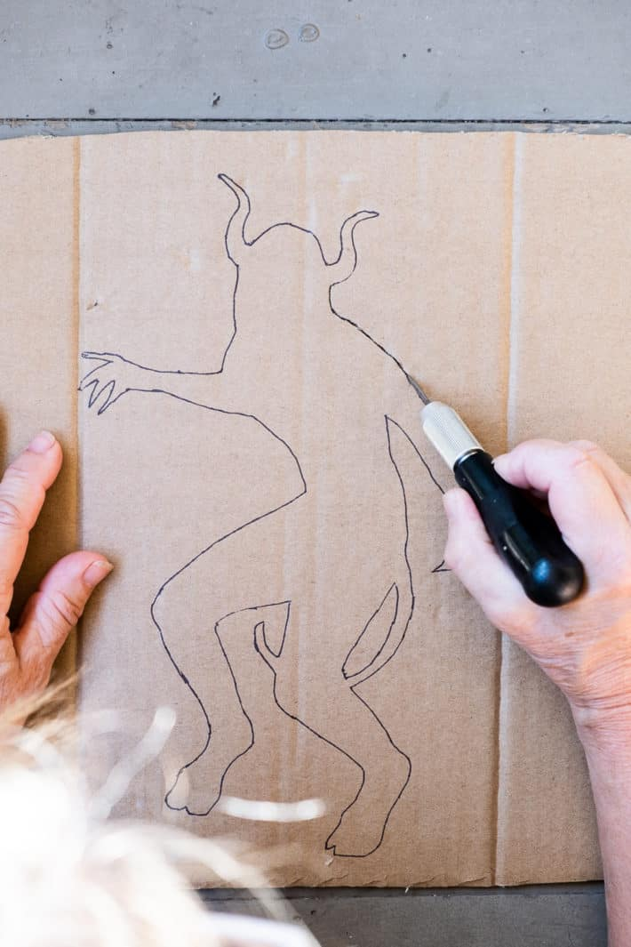 Cutting out cardboard stencil with XACTO knife.